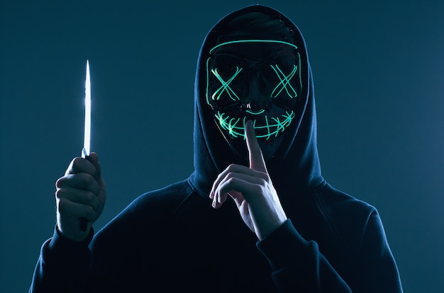 Anonymous criminal man with kitchen knife in a black hoodie and neon mask