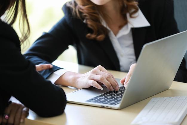 사무실에서 함께 프로젝트 작업을 하는 동안 랩톱 노트북 컴퓨터 화면을 가리키는 익명의 여성 관리자. 교육 및 팀 작업 개념입니다.