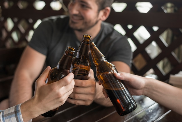 Anonymous friends clinking bottles and bar table