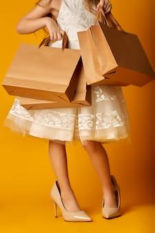 Анонимная девушка в стильной одежде и огромных туфлях на высоком каблуке берет бумажный пакет