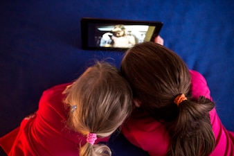 Anonymous girls watching video on tablet