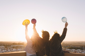 Anonymous girls with balloons on roof