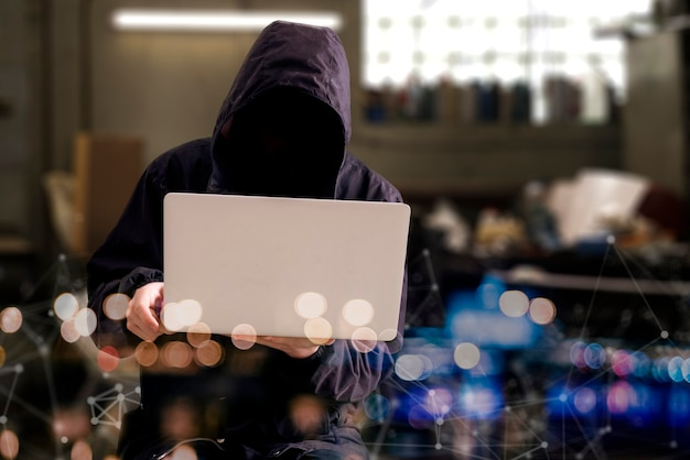 A anonymous hacker person in the hood with computer, digital information breaking