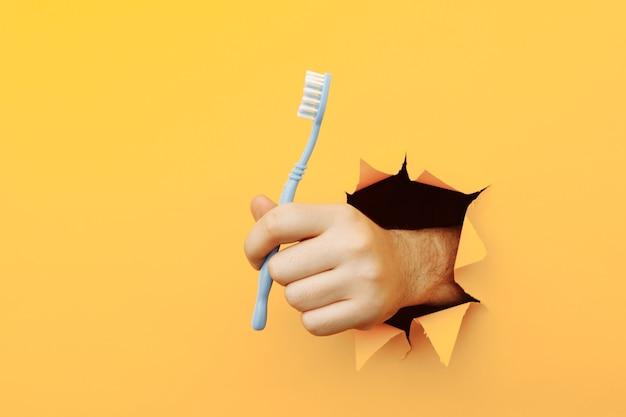 破れた紙の穴に伸ばした歯ブラシを持っている匿名の手。