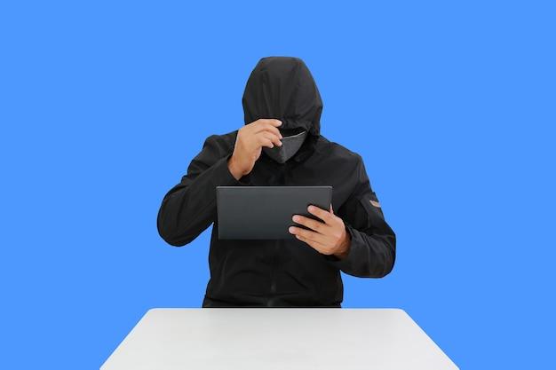 Анонимные хакеры с капюшоном взламывают данные планшета, изолированные на синем фоне. изображение с обтравочным контуром