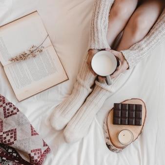 Signora anonima con latte vicino a libro e cioccolato