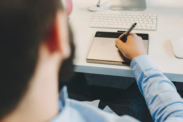 스타일러스를 사용하여 사무실 책상에 앉아 그래픽 태블릿에 스케치를 그리는 익명의 남성 디자이너