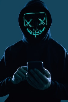 Anonymous man in a black hoodie and neon mask hacking into a smartphone