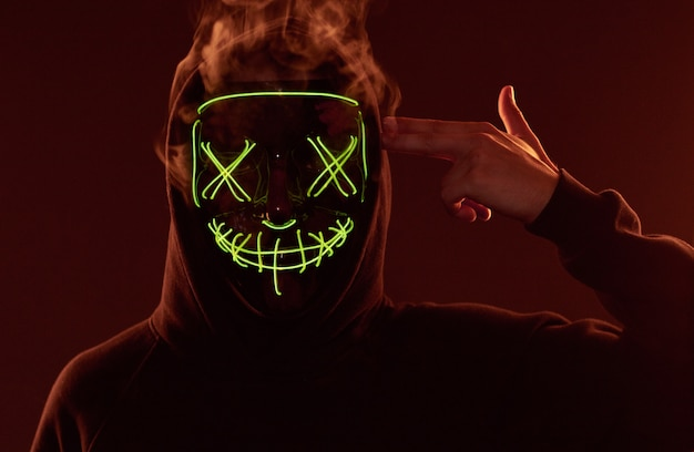Anonymous man hiding his face behind neon mask in a colored smoke