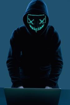 Анонимный мужчина в черной балахоне и неоновой маске взломал компьютер