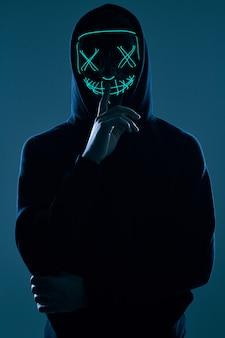 네온 마스크 뒤에 그의 얼굴을 숨기고 검은 까마귀의 익명 남자