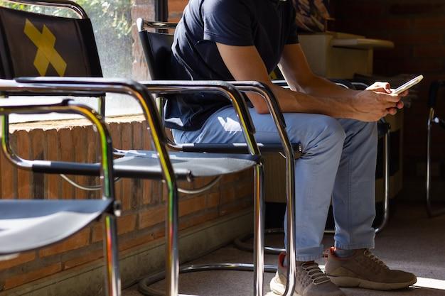 医者の待合室で携帯電話で座っているブルージーンズとtシャツの匿名の男