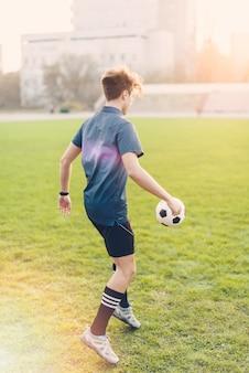 Uomo anonimo che calcia la palla
