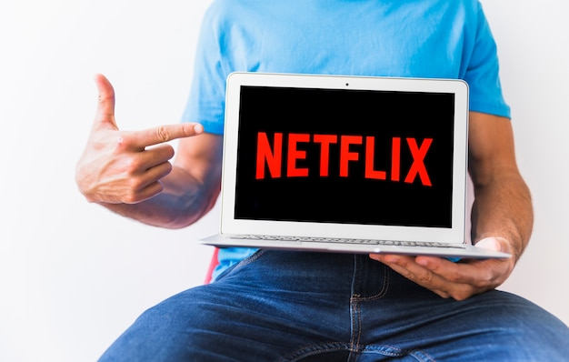 Netflix 로고를 가리키는 익명의 남자