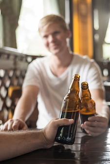 Anonymous men clinking bottles at pub table