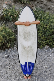 Anonymous person hugging surfboard on shore