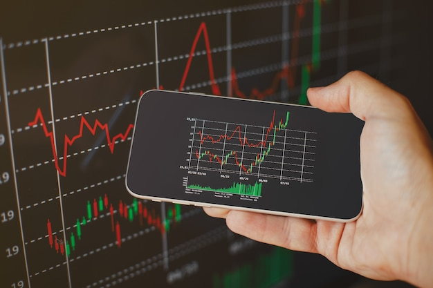 モバイル画面で暗号通貨の成長グラフを表示している匿名の人。株式市場