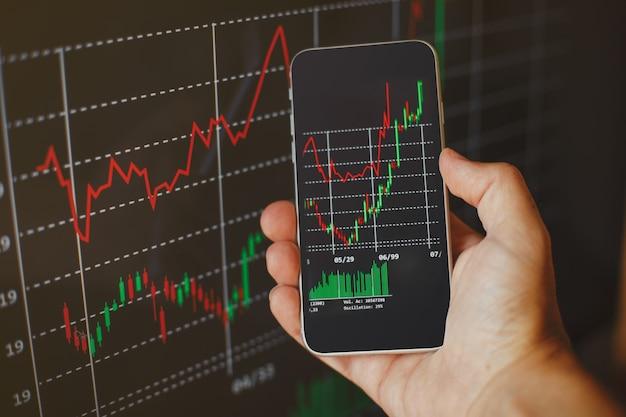Анонимный человек показывает график роста криптовалюты на экране мобильного телефона. фондовый рынок