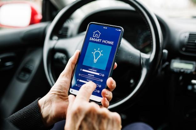 차의 운전석에 앉아 화면에 스마트 홈 앱이 있는 휴대폰을 사용하는 익명의 사람