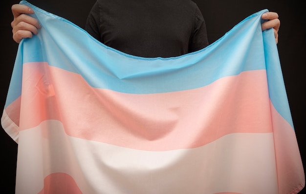 トランスジェンダープライドフラグ、コンセプト画像を持つ匿名の人