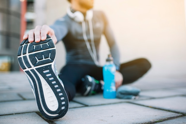 Anonymous sportsman stretching on pavement