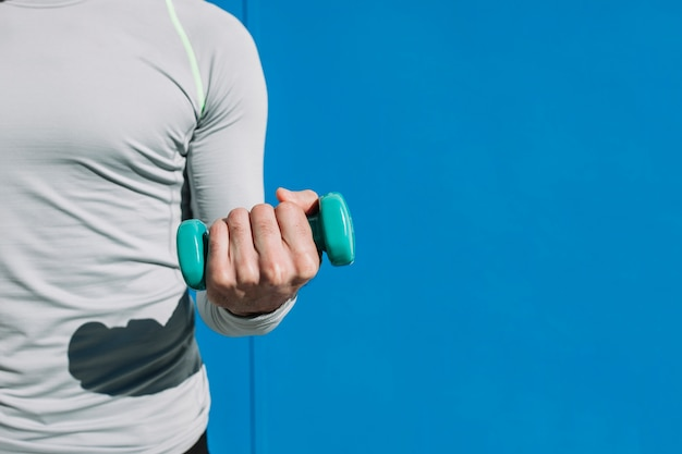 Anonymous sportsman with small dumbbell