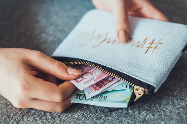 Anonymous woman counting new modern euro bills