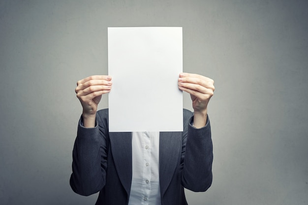 Anonymous woman covering face with  paper sheet