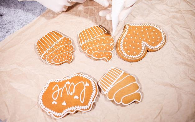 キッチンで自家製ジンジャーブレッドクッキーを飾る匿名の女性