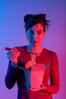 파란색과 빨간색 불빛과 함께 스튜디오에서 젓가락으로 점심 아시아 국수 상자를 들고 익명의 여자