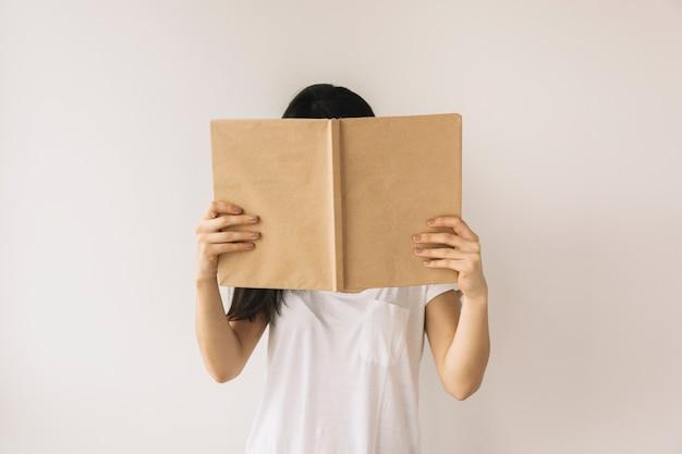 Anonymous woman reading near white wall