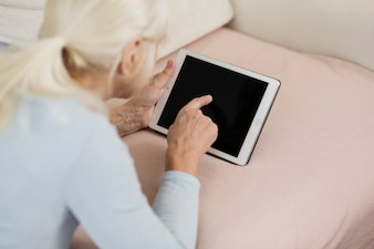 Anonymous woman resting on sofa with tablet