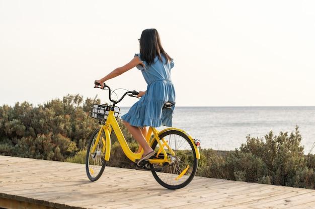 海の近くの遊歩道に沿って黄色い自転車に乗る匿名の女性