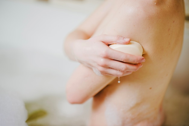 Anonymous woman taking bath with soap