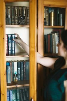 本棚から匿名の女性が本を取って