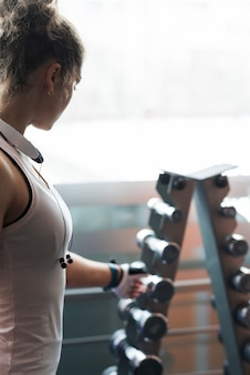 Anonymous woman taking dumbbell from rack