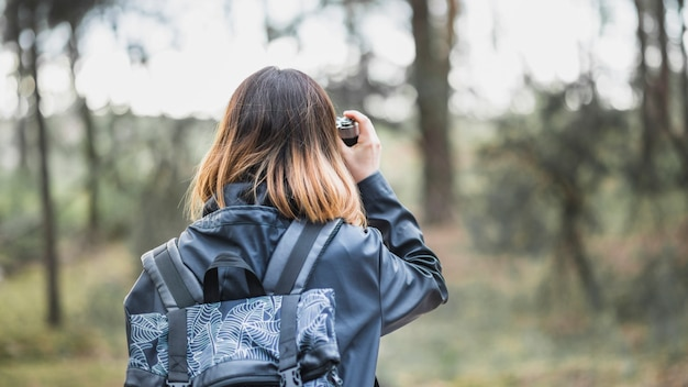 Anonymous woman taking photos in forest