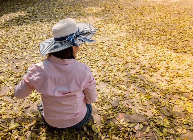 Анонимные женщины в голубых шапках сидят одни. расслабьтесь и наслаждайтесь в парке, полном листьев по всей земле.