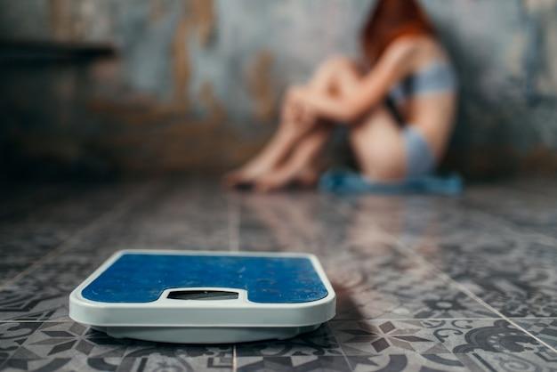 Больная женщина, страдающая анорексией, сидит на полу, потеря веса, анорексия. концепция сжигания жира или калорий, медицинское заболевание