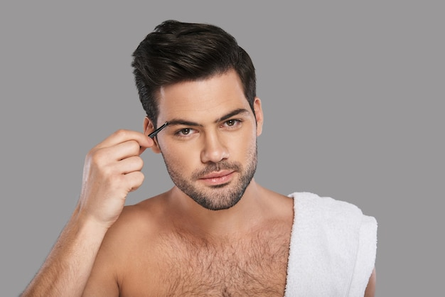 Another beauty treatment. handsome young man looking at camera and applying eyebrow tweezers while standing against grey background
