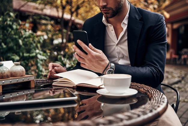 또 다른 비즈니스 메시지. 야외 레스토랑에 앉아 있는 동안 스마트 폰을 사용하여 스마트 캐주얼 차림의 젊은 남성 클로즈업