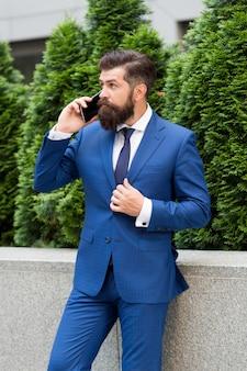 別のクライアント。成功した保険代理店。あなたの将来の雇用主。ハンサムなマネージャーはスマートフォンを使用しています。外のフォーマルな服装の男。全米リアルター協会加入者のボタンのジャケット。現代の生活の概念。自信の肖像。