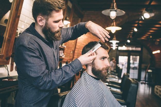 Еще одна фотография бородатых парней в парикмахерской. один мужчина подстригает другого. процедура очень длинная, но интенсивная.