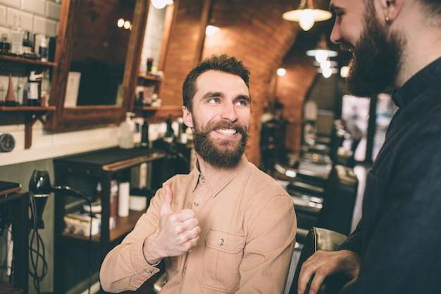 Еще одна картина счастливого клиента смотрит на парикмахера и улыбается. он доволен результатом. он показывает свой большой палец до парикмахера.
