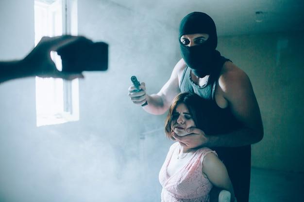 Еще одна фотография похитителя и его жертвы. человек носит маску. он стоит позади девушки и держит пистолет. они смотрят в камеру. другой мужчина записывает видео. девушка связана веревками