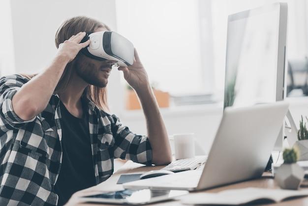 別の現実がここにあります!創造的なオフィスの彼の机に座っている間彼の仮想現実のヘッドセットを調整する長い髪のハンサムな若い男