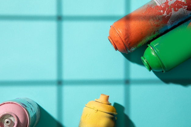 Another top view of used spray paint cans on cyan background with grid shadows and free space for text