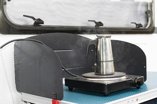 Еще один способ путешествовать в отпуск. приготовление кофе в караване на свежем воздухе.
