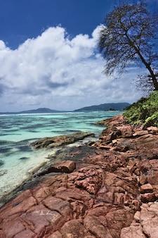 Вид на красные скалы на берегу моря в anse la blague, остров праслин, сейшельские острова
