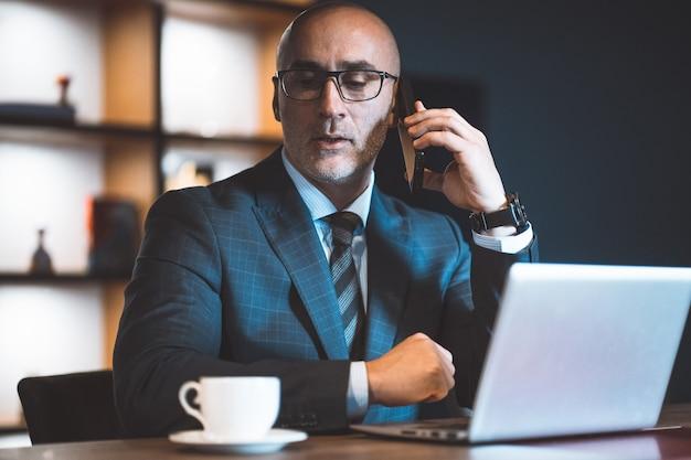 Отвечая на телефонный звонок, бизнесмен сделал перерыв в работе и смотрит на чашку кофе возле ноутбука.